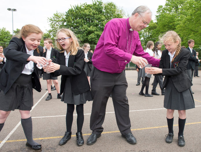Bishop Richard and pupils taking part in the water relay