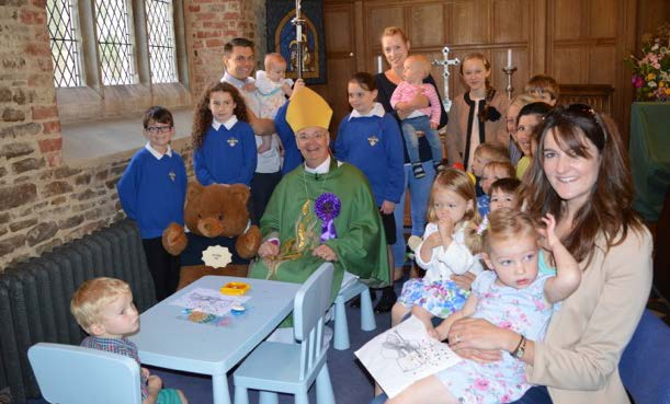 Bishop Richard wearing his rosette and seated in St Mary's children's corner