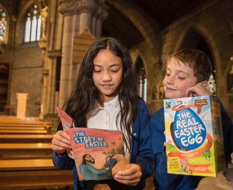Children with 'The Real Easter Egg' and book